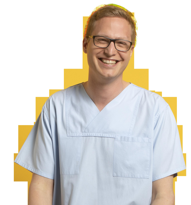 Foto mit Mann. Er lächelt und trägt weiße Berufskleidung der Medizin und Pflege.