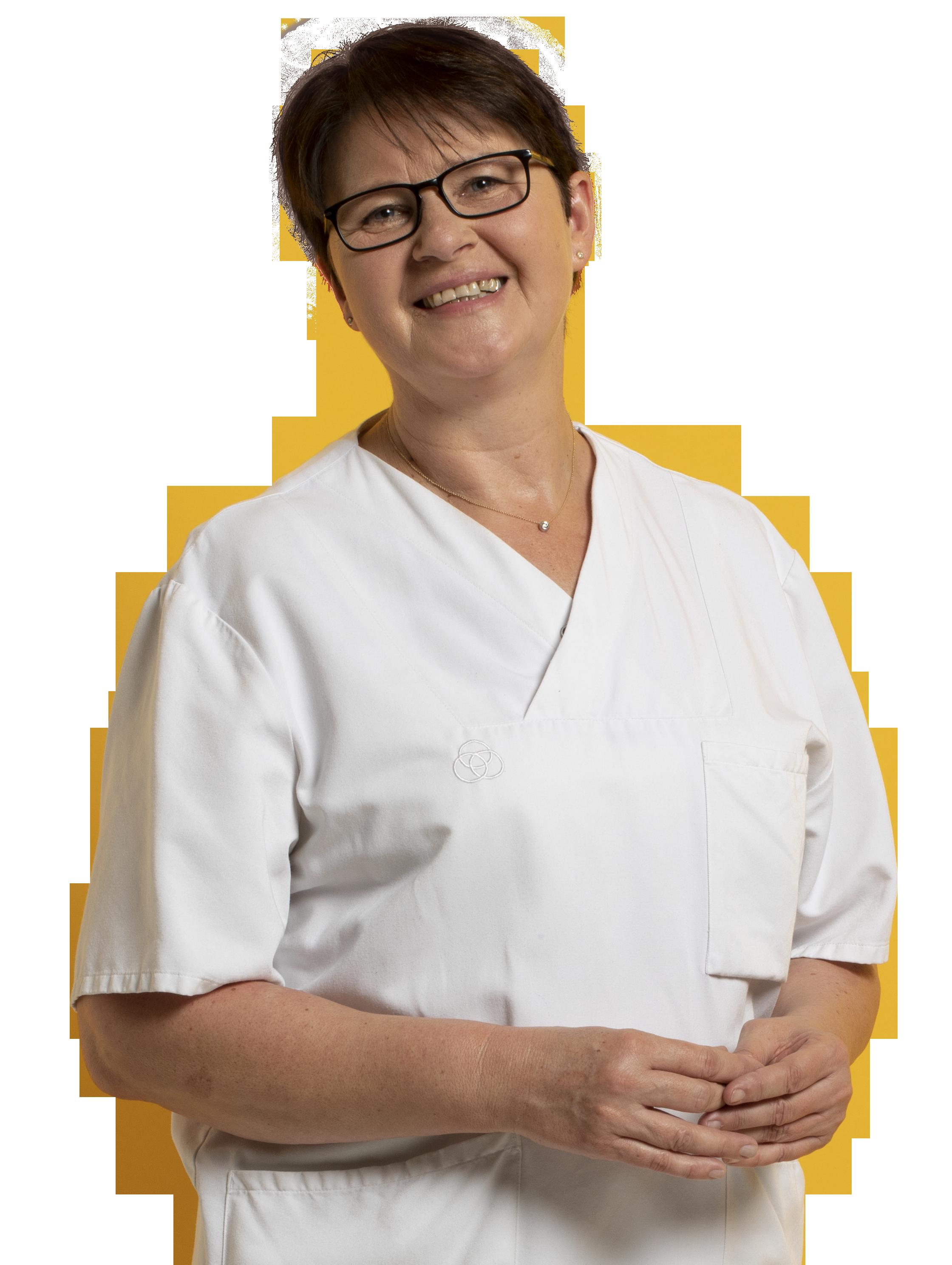 Foto mit Frau. Sie lächelt und trägt weiße Berufskleidung der Medizin und Pflege.